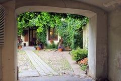 Båge i gammalt byhus, liten gård och blommor Royaltyfri Foto