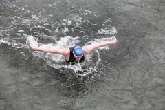 Bügeln Sie Mannschwimmer in der Kappe und in Wetsuit, die Schmetterlingsanschlag durchführend atmet Lizenzfreie Stockfotografie