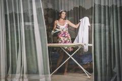 Bügelnde Kleidung der Frau Stockfotos