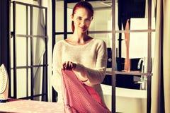 Bügelnde Kleidung der rothaarigen jungen Schönheit Stockfoto