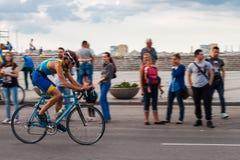 Bögen rider en cykel förbi folket Royaltyfri Foto