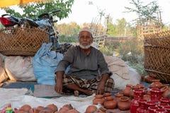 Bhadarsa Uttar Pradesh/Indien - April 3, 2019: En man poserar för ett foto, medan sälja krukmakeri på en festival som omger NANDI arkivfoton