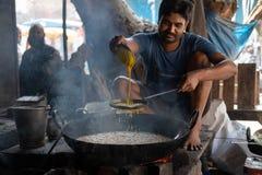 Bhadarsa, Uttar Pradesh/la India - 2 de abril de 2019: Frys de un hombre encima del lado de la calle del jalebi en Bhadarsa fotografía de archivo libre de regalías