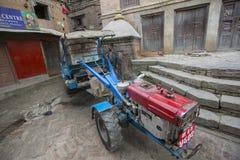 BHAKTAPUR,尼泊尔-尼泊尔人和他的拖拉机在街道上 库存图片