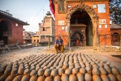 BHAKTAPUR,尼泊尔-工作在他的瓦器车间的尼泊尔人 库存图片