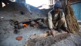 BHAKTAPUR,尼泊尔-工作在他的瓦器车间的尼泊尔人 免版税库存照片