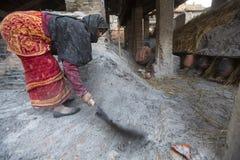 BHAKTAPUR,尼泊尔-工作在他的瓦器车间的尼泊尔妇女 免版税库存图片