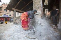 BHAKTAPUR,尼泊尔-工作在他的瓦器车间的尼泊尔妇女 免版税图库摄影
