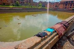 BHAKTAPUR,尼泊尔- 2017年11月04日:关闭与一个人为池塘的传统都市场面有鸭子游泳的 库存图片