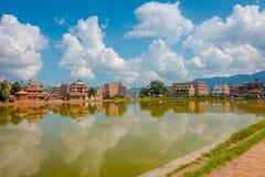 BHAKTAPUR,尼泊尔- 2017年11月04日:关闭与黄色一个人为池塘的被弄脏的传统都市场面  免版税库存照片