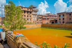 BHAKTAPUR,尼泊尔- 2017年11月04日:关闭与黄色水一个人为池塘的传统都市场面在 免版税图库摄影