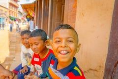 BHAKTAPUR,尼泊尔- 2017年11月04日:关闭微笑,对户外的小组孩子看照相机的和一个男孩 库存照片