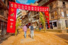 BHAKTAPUR,尼泊尔- 2017年11月04日:在他们的商店里面的店主广场围拢的老大厦接近 库存照片