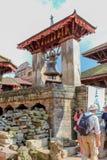 Bhaktapur,尼泊尔- 2016年11月04日:在咆哮附近响铃的游人在Durbar广场,加德满都,尼泊尔 库存照片
