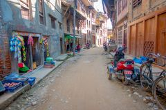 BHAKTAPUR,尼泊尔- 2017年11月04日:街道与有些摩托车的食物市场在a的老和含沙街道停放了 免版税库存图片
