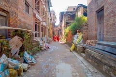 BHAKTAPUR,尼泊尔- 2017年11月04日:走在老和肮脏的街道的未认出的妇女在一个土气镇,有大袋的 免版税库存照片