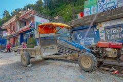 BHAKTAPUR,尼泊尔- 2017年11月04日:走接近一辆小卡车的未认出的人民在一个小镇,谷停放了 库存图片