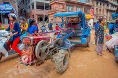 BHAKTAPUR,尼泊尔- 2017年11月04日:走接近一辆小卡车的未认出的人民在Taumadhi在Bhaktapur摆正 免版税图库摄影