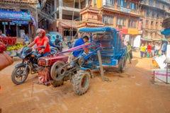 BHAKTAPUR,尼泊尔- 2017年11月04日:走接近一辆小卡车的未认出的人民在Taumadhi在Bhaktapur摆正 库存图片