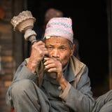 BHAKTAPUR,尼泊尔-未认出的尼泊尔人画象在街道上抽烟 库存照片