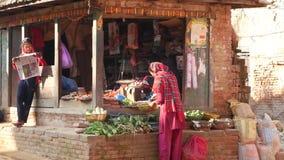 Bhaktapur, Катманду, Непал - люди 18-ое октября 2018 азиатские продавая товары в национальных одеждах, овощах плода утра сток-видео