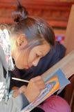 BHAKTAPUR, ΝΕΠΑΛ - 29 ΔΕΚΕΜΒΡΊΟΥ 2014: Ένας τοπικός καλλιτέχνης που χρωματίζει ένα παραδοσιακό θιβετιανό Thangka Στοκ Εικόνες