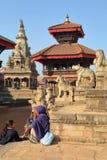 BHAKTAPUR, НЕПАЛ - 29-ОЕ ДЕКАБРЯ 2014: Квадрат Durbar при непальские женщины наслаждаясь солнцем Стоковые Изображения