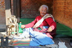 BHAKTAPUR, НЕПАЛ - 29-ОЕ ДЕКАБРЯ 2014: Шерсть старухи закручивая вне ее дома Стоковая Фотография RF
