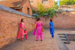 BHAKTAPUR, НЕПАЛ - 4-ОЕ НОЯБРЯ 2017: Неопознанная группа в составе девушки нося типичные одежды на окружать outdoors старой Стоковое фото RF