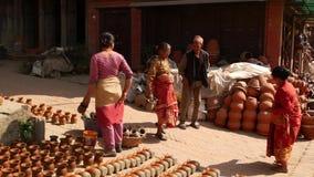 BHAKTAPUR, KATHMANDU, NEPAL - 18 October 2018 Artisans. People on local street market selling craft pieces of clay stock video footage