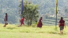 BHAKTAPUR, KATHMANDU, NEPAL - 18 October 2018 Child buddhist monks playing football on green meadow. Group of boys of. Children monastery running on green lawn stock video footage