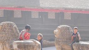 BHAKTAPUR, KATHMANDU, NEPAL - 18 October 2018 Little cheerful children girls sitting on stone sculpture, playing in yard stock video