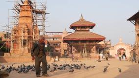 BHAKTAPUR, KATHMANDU, NEPAL - 18 October 2018 Man feeding pigeons on royal square. Mature man feeding birds on royal stock video footage