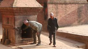 BHAKTAPUR, KATHMANDU, NEPAL - 18 October 2018 Newar people visiting hindu temple for worshiping in traditional clothes stock footage