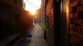 BHAKTAPUR, KATHMANDU, NEPAL - 18 October 2018 Pedestrians on narrow street in sunrise. Ethnic man and woman walking on stock video