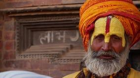 BHAKTAPUR, KATHMANDU, NEPAL - 18 October 2018 Senior Sadhu man with face painted. Elderly Sadhu man wearing colorful stock footage