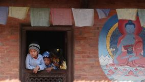 BHAKTAPUR, KATHMANDU, NEPAL - 18 Października 2018 dzieciaki w okno starzejąca się świątynia Mali etniczni dzieci w ornamentacyjn zbiory