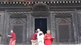 BHAKTAPUR, KATMANDU, NEPAL - 18 de octubre de 2018 gente de Newar que visita el templo hindú para adorar en ropa tradicional metrajes