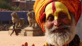 BHAKTAPUR, KATMANDU, NEPAL - 18 de octubre de 2018 hombre mayor de Sadhu con la cara pintada El llevar mayor del hombre de Sadhu  almacen de video