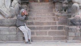 BHAKTAPUR, KATMANDU, NEPAL - 18 de octubre de 2018 pobre hombre en los pasos de piedra Pobre hombre envejecido que se sienta en p almacen de metraje de vídeo