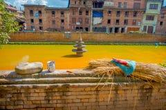 BHAKTAPUR, NÉPAL - 4 NOVEMBRE 2017 : Fermez-vous de la scène urbaine traditionnelle avec un étang artificiel de l'eau jaune à Photo libre de droits