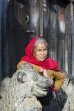 BHAKTAPUR, NEPAL ï ¿ ½ LISTOPAD 21: Nepalska kobieta odpoczywa na statui Fotografia Royalty Free