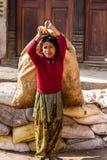 BHAKTAPUR, NEPAL - APRIL 19, 2013: Kinderarbeid in Azië Meisje te Royalty-vrije Stock Fotografie