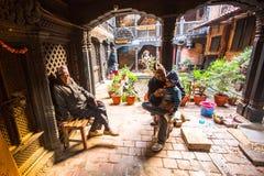 BHAKTAPUR, NEPAL - armen in zijn huis stock foto