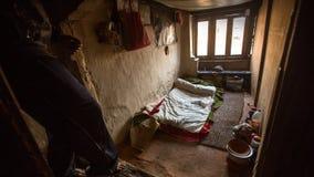 BHAKTAPUR, NEPAL - armen in zijn huis stock afbeelding
