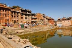 BHAKTAPUR NEPAL - 15 DE NOVEMBRO DE 2016: Casas newar nepalesas tradicionais perto da lagoa verde em Bhaktapur, Nepal Imagem de Stock Royalty Free