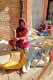 BHAKTAPUR, NEPAL - DECEMBER 29, 2014: Een jonge vrouw die de korrel buiten haar huis in de straat verpletteren Stock Foto