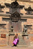 BHAKTAPUR, NEPAL - DECEMBER 30, 2014: A Nepalese woman sitting in front of a traditional house Royalty Free Stock Photo