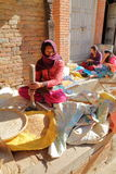 BHAKTAPUR, NEPAL - DECEMBER 29, 2014: A young woman pounding the grain outside her home in the street Stock Photo