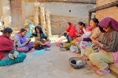 BHAKTAPUR, NEPAL - DECEMBER 29, 2014: Young women knitting outside their home Stock Photo